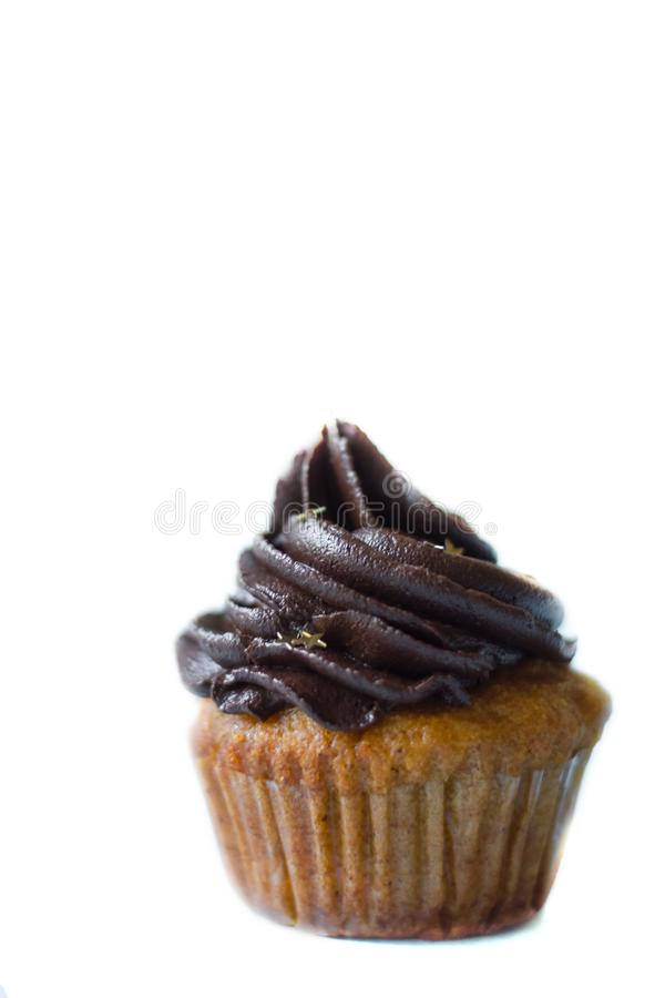 Birthday cupcake with the chocolate frosting on the top. Birthday cupcake with chocolate frosting on the top on on white stock photography