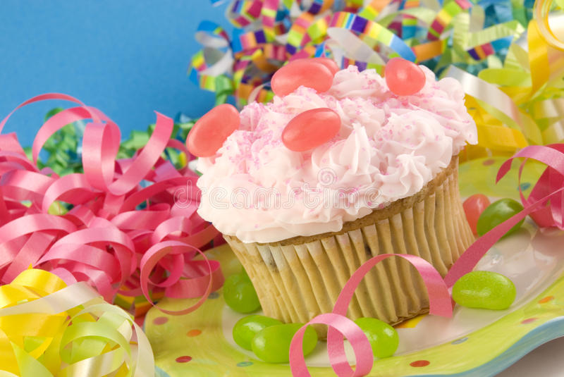 Birthday Cupcake with Colorful Decorations. A birthday cupcake with colorful party decorations, horizontal with copy space, selective focus royalty free stock image