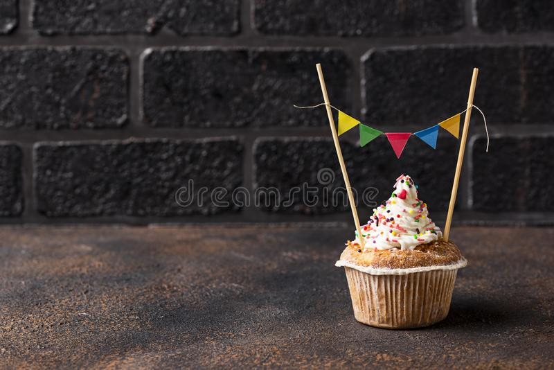Birthday cupcake with cream and colorful garland stock images