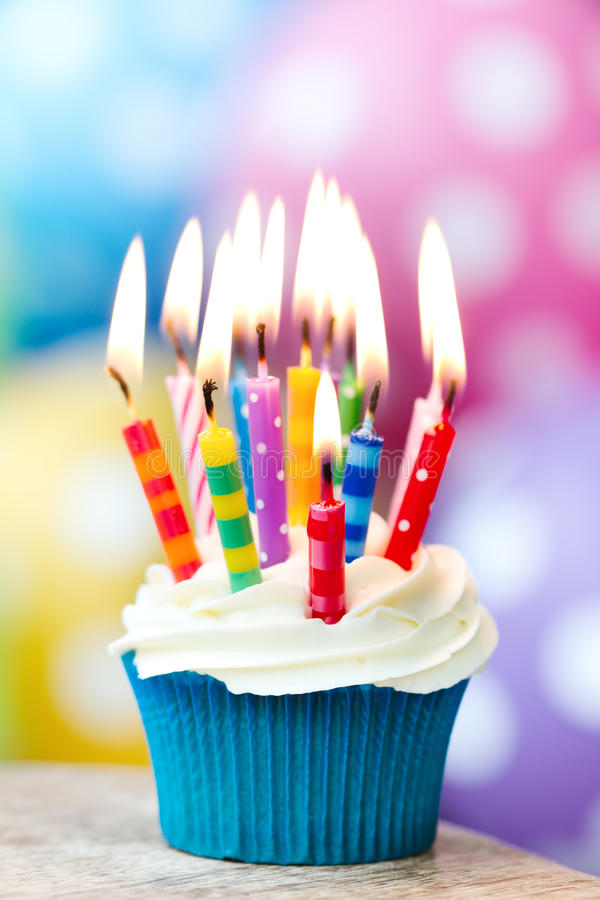 Birthday cupcake. Cupcake decorated with colorful birthday candles stock photography