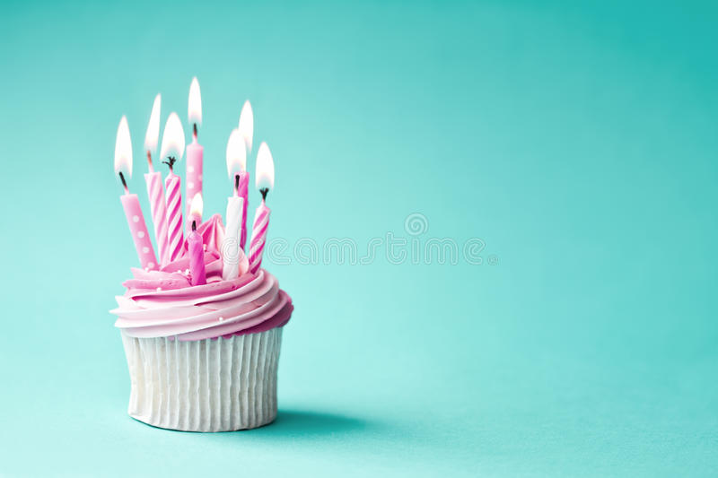 Birthday cupcake. Cupcake decorated with pink birthday candles stock image