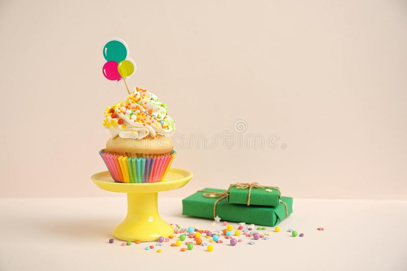 Birthday cupcake and gift boxes on background. Birthday cupcake and gift boxes on beige background stock images