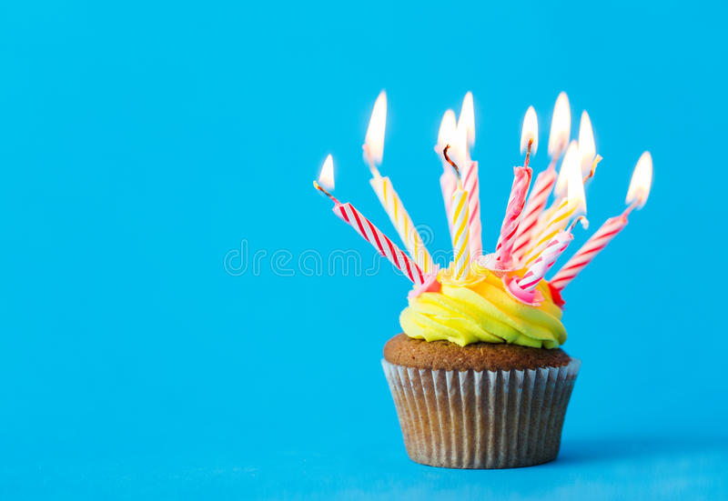 Birthday cupcake with many burning candles. Holiday, celebration, greeting and party concept - birthday cupcake with many burning candles over blue background stock image