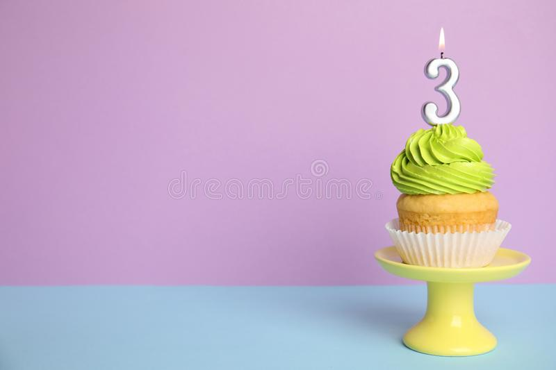 Birthday Cupcake With Number Three Candle On Stand Against