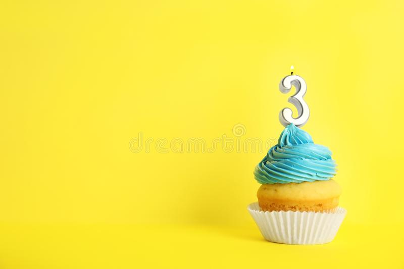 Birthday cupcake with number three candle on yellow background royalty free stock images