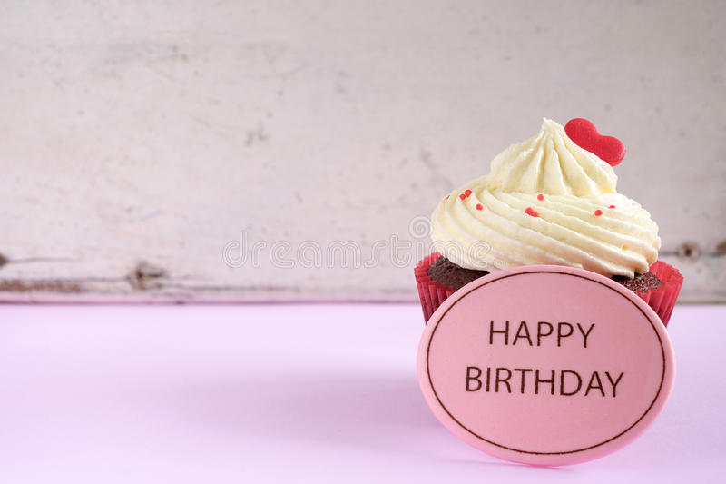Birthday cupcake with red heart. Over vintage wooden background with copy space stock photos
