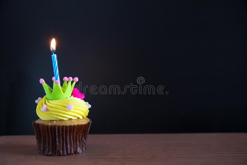 Birthday cupcake with a single blue candle.Cupcake with yellow cream. And heart for love valentines.green crown cupcakes with cream cheese frosting and a red stock image