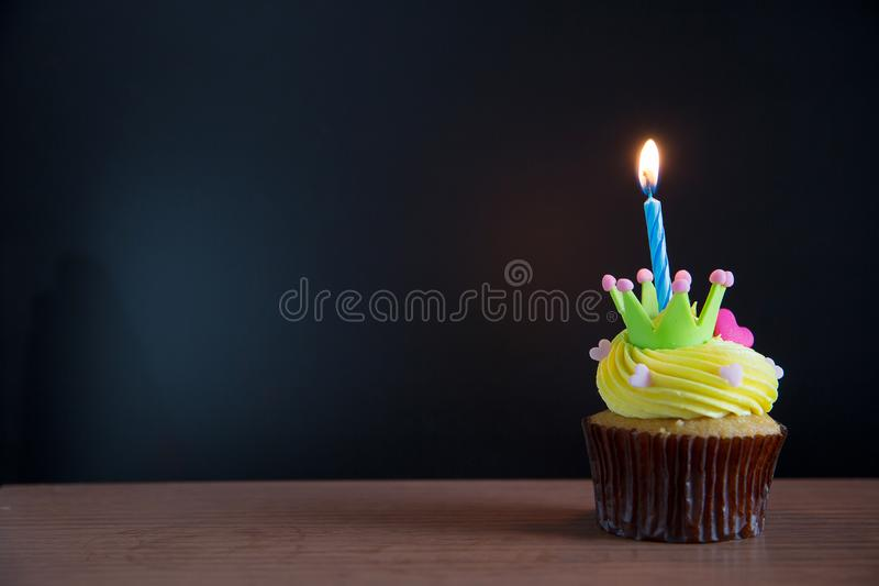 Birthday cupcake with a single blue candle.Cupcake with yellow cream. And heart for love valentines.green crown cupcakes with cream cheese frosting and a red stock images