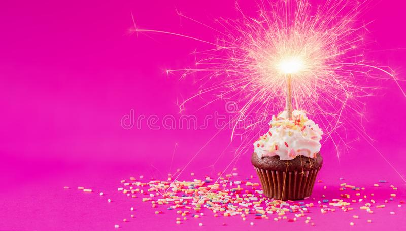 Birthday Cupcake with a sparkler at pink background stock photography