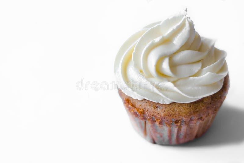 Birthday cupcake with the white chocolate frosting on the top isolated. Birthday cupcake with white chocolate frosting on the top on the table royalty free stock image