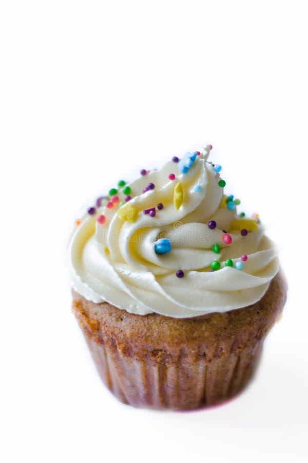Birthday cupcake with the white chocolate frosting on the top isolated. Birthday cupcake with white chocolate frosting on the top on the table royalty free stock photos