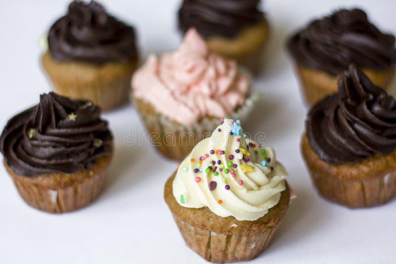 Birthday cupcake with the white chocolate frosting on the top isolated. Birthday cupcake with white chocolate frosting on the top on the table stock photos