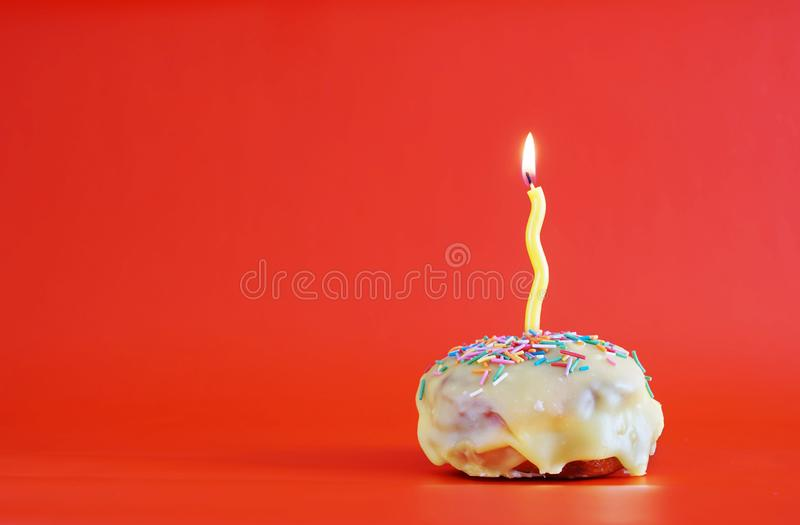 Birthday cupcake with a yellow burning candle on vivid red background stock image
