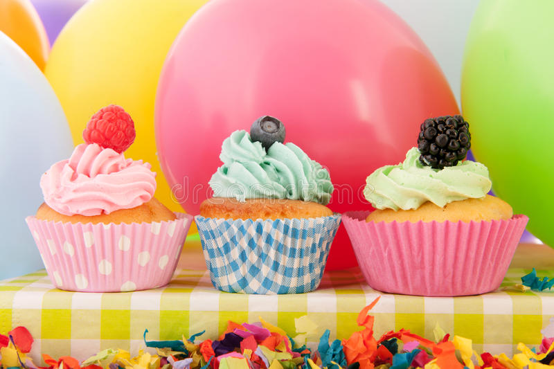 Birthday cupcakes. With balloons and confetti stock image