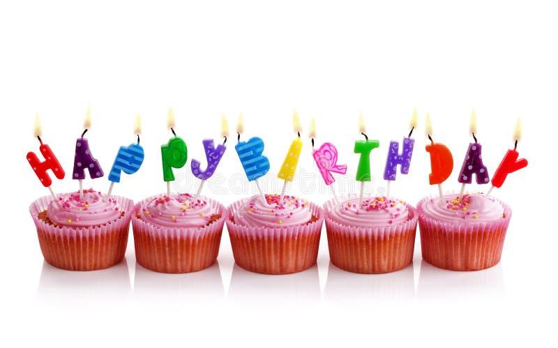 Birthday cupcakes. Happy birthday candles on pink cupcakes on white stock photos