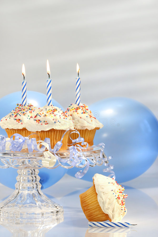 Birthday cupcakes with blue candles stock image