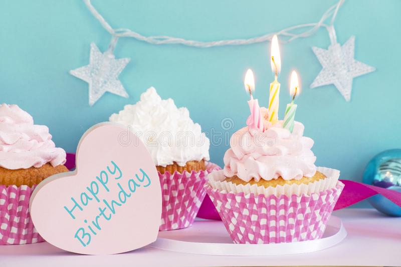 Birthday cupcakes. With the burning candle stock images