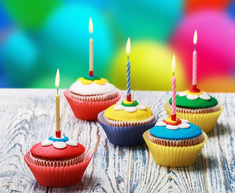 Birthday cupcakes with burning candles. On the background of balloons stock images