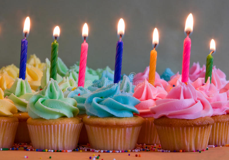 Birthday cupcakes with candles. Rainbow cupcakes with lit birthday candles stock images