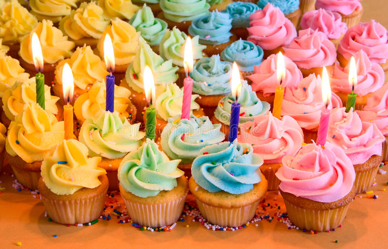 Birthday cupcakes with candles. Rainbow cupcakes with lit birthday candles stock image