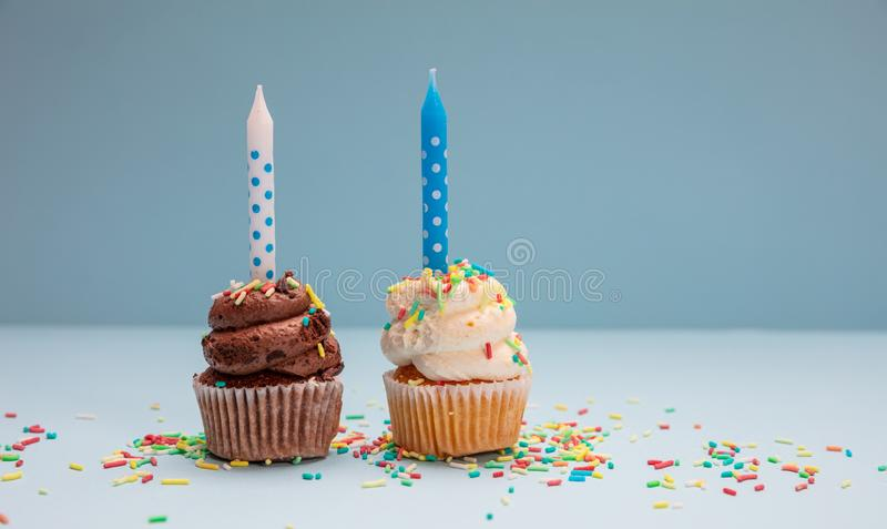 Birthday cupcakes with candles on blue pastel background, copy space stock image