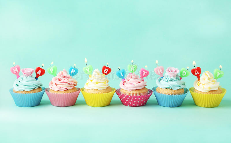 Birthday cupcakes with candles on green background. Birthday cupcakes with candles on the green background royalty free stock images