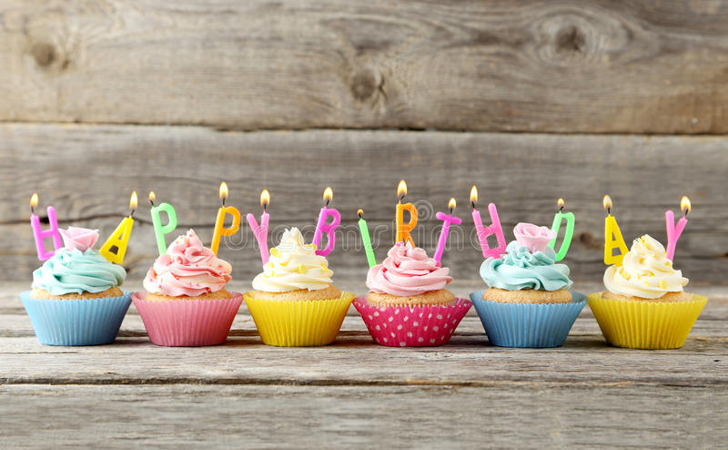 Birthday cupcakes. With candles on grey wooden background royalty free stock photos