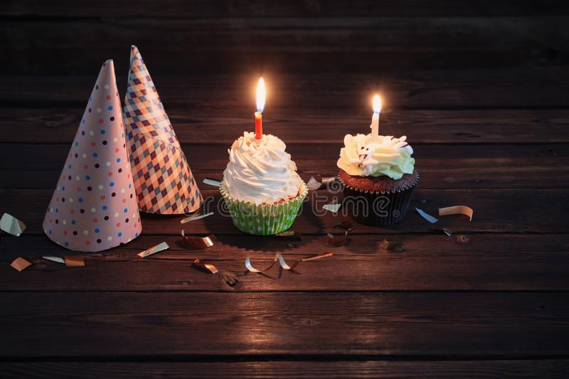 Birthday cupcakes with candles on dark  wooden background. Birthday cupcakes with candles on old dark  wooden background stock photo