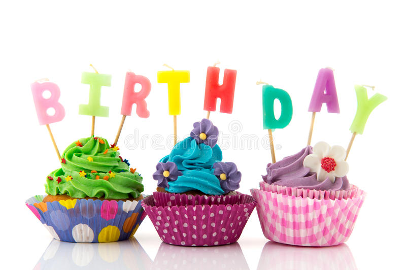 Birthday cupcakes. Colorful birthday cupcakes with candles isolated over white background stock images