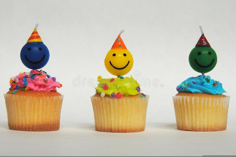 Birthday cupcakes. With happy face candles stock photos