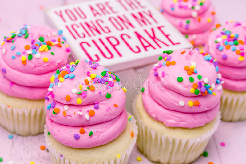 Birthday Cupcakes with Pink Frosting. 5 fresh baked vanilla cupcakes with pink swirled strawberry frosting topped with colorful sprinkles and wooden box with stock photo