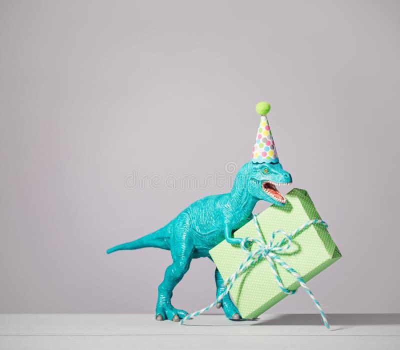 Birthday Dinosaur. T-rex dinosaur toy with birthday hat holding gift on a light grey background stock photos