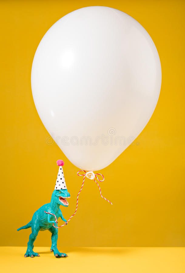 Birthday Dinosaur. Teal dinosaur toy with birthday hat holding a white balloon on a yellow background stock photo
