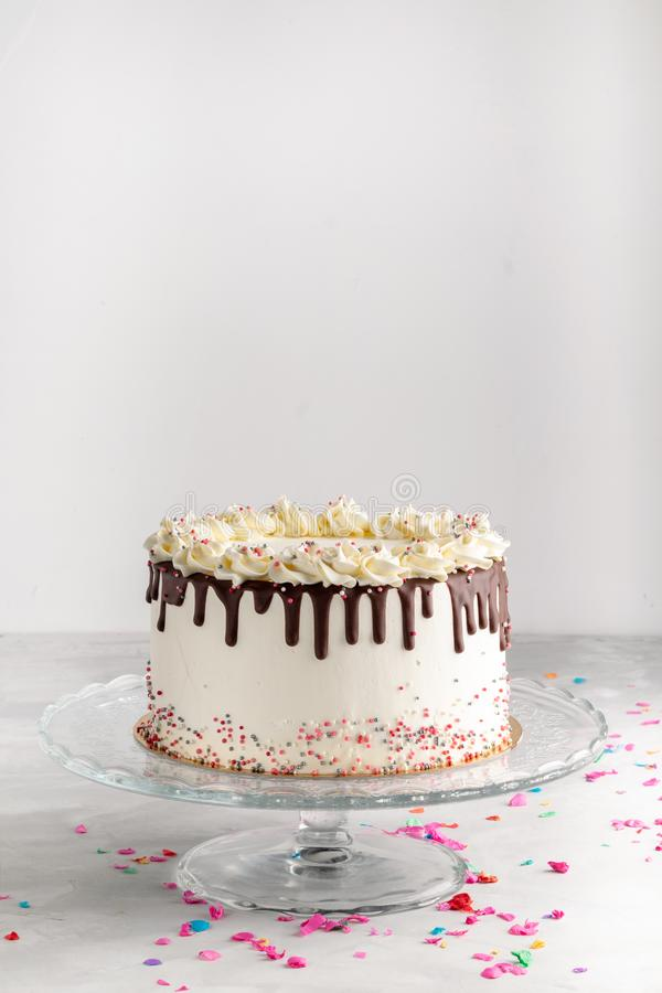 Birthday Drip Layered Cake with chocolate ganache and sprinkles on a white background with party decor. Horizontal. Copy space. Ce. Lebration concept. Trendy royalty free stock photography