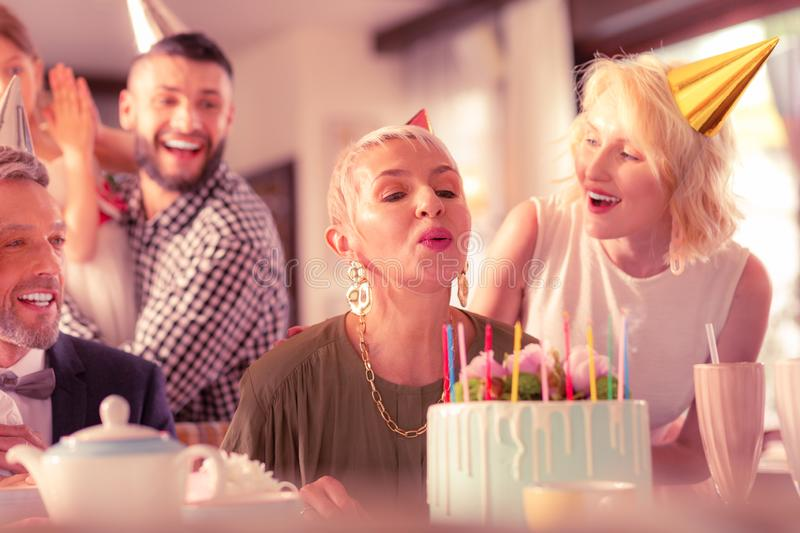 Aged woman blowing at candles celebrating birthday with family stock photography