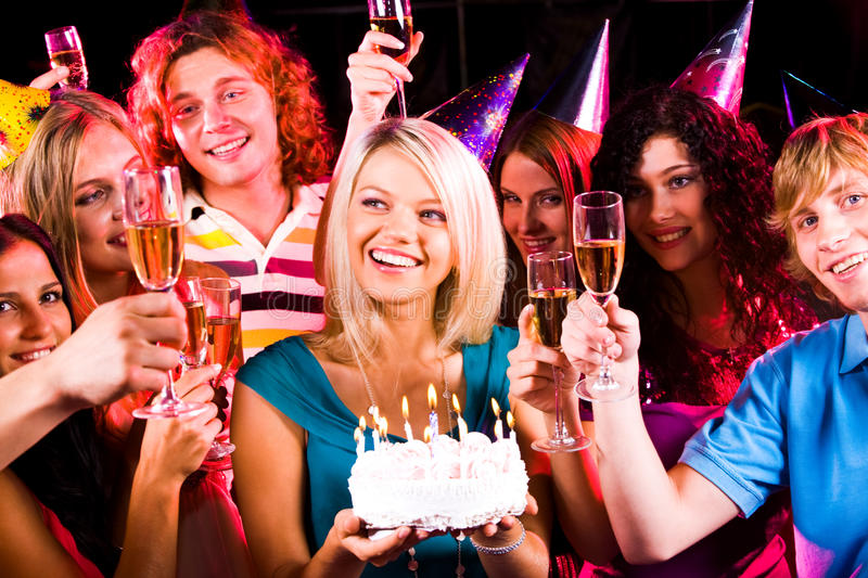 Birthday fare. Portrait of joyful girl holding birthday cake surrounded by friends with flutes of champagne stock photo