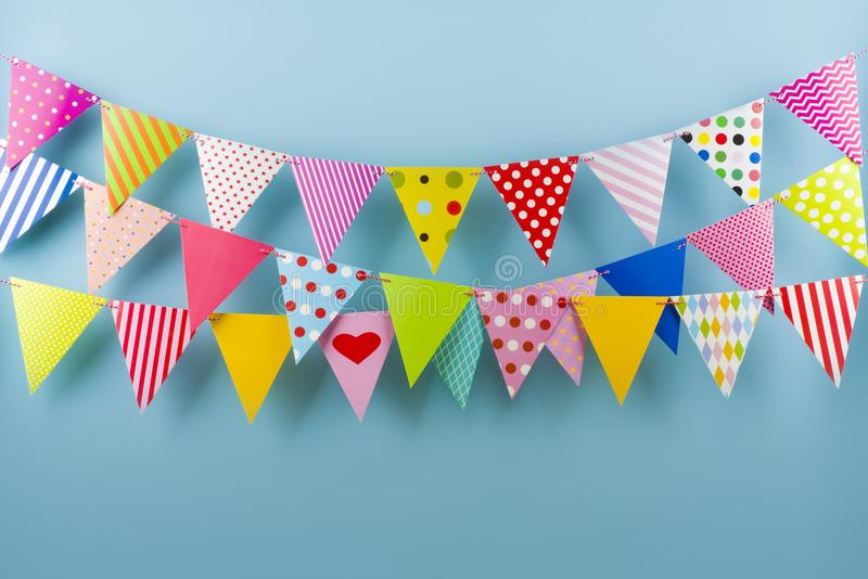 Birthday fest garlands from colorful triangular flags on blue background royalty free stock photography