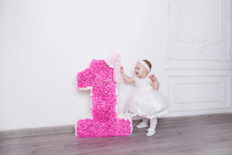 Birthday, the first year. A little girl is standing on her birthday near the number one royalty free stock photo