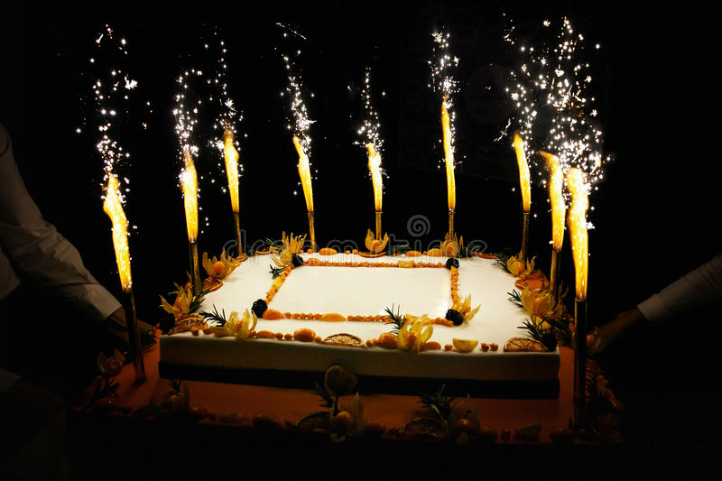 Birthday fruit cake with fireworks candles. Rectangular Birthday fruit cake with fireworks candles stock photo