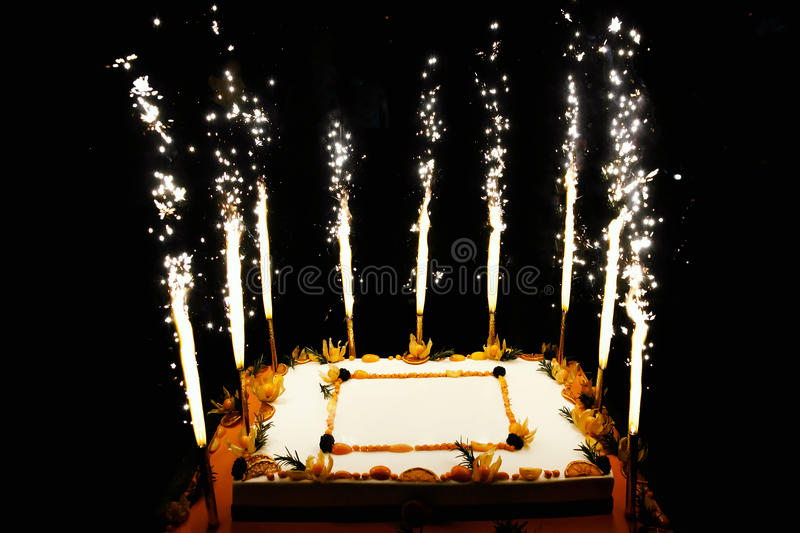 Birthday fruit cake with fireworks candles. Rectangular Birthday fruit cake with fireworks candles royalty free stock photos