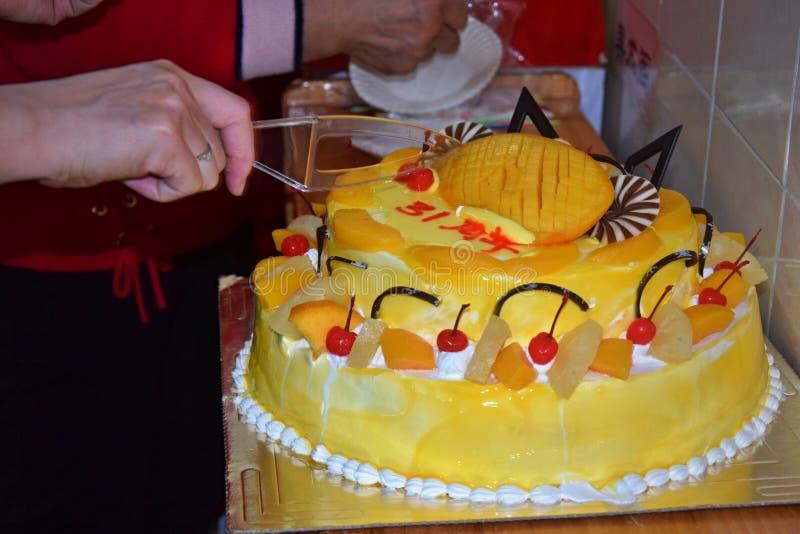 Birthday fruit cake. Hand cutting a birtday cake. Birthday fruit cake. Mango birthday cake. Hand portions out a birtday cake. Happy birthday stock images
