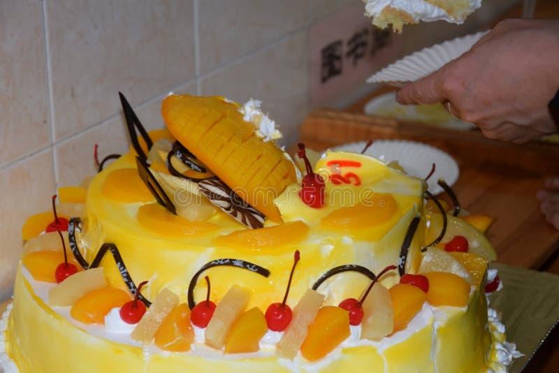 Birthday fruit cake. Hand cutting a birtday cake. Birthday fruit cake. Mango birthday cake. Hand portions out a birtday cake. Happy birthday.nn stock photo