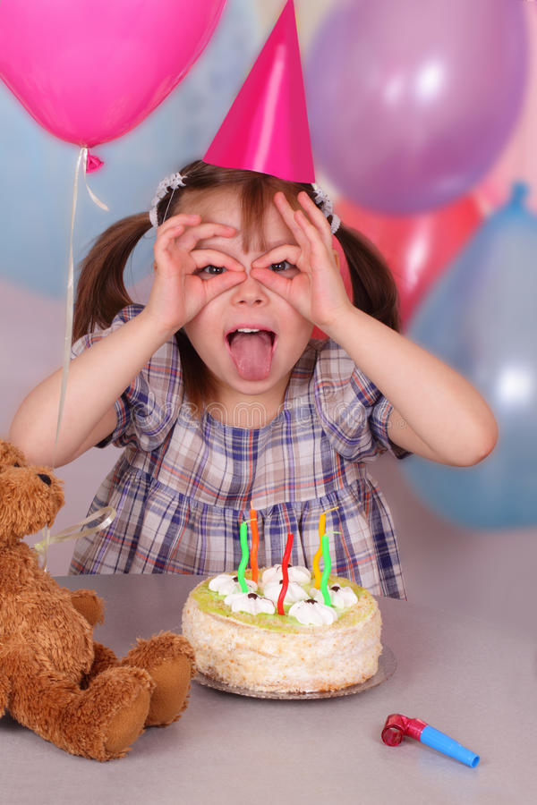 Birthday of funny little girl. In the cap royalty free stock image