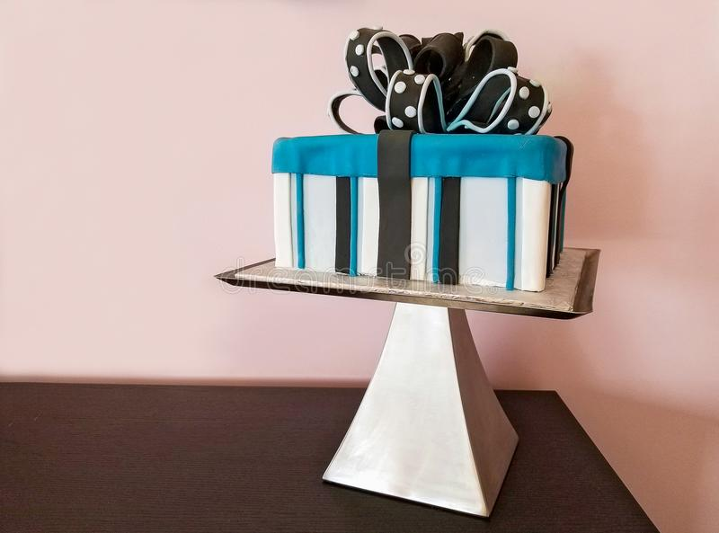Birthday gift cake with bow. Striped birthday cake gift cake with fondant bow on pedestal cake plate royalty free stock photography