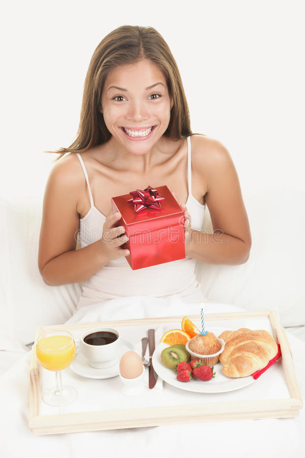 Birthday gift - happy smiling woman. Birthday gift woman getting morning surprise in bed with present and breakfast. Young smiling excited and happy woman stock image