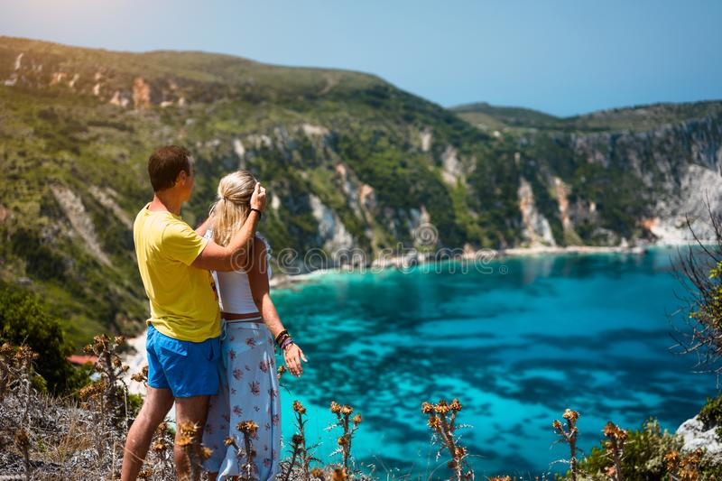 Birthday gift. Young man closing hes girlfriend eyes in front of gorgeous seascape panorama of blue lagoon. Couple love. Birthday gift. Young men closing hes stock images