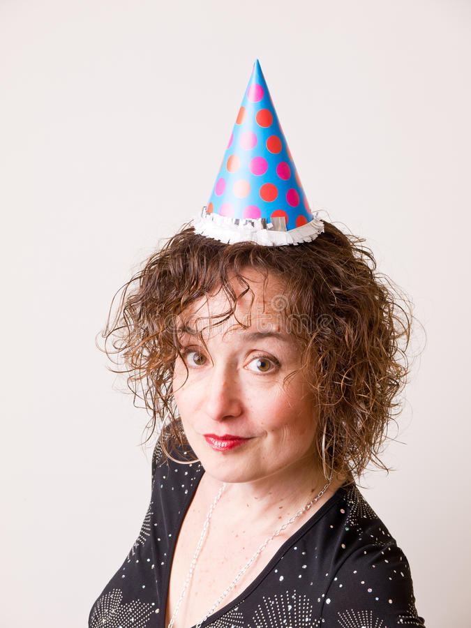 Birthday Girl. A woman dressed up for her birthday or New Year's Eve wearing a party hat royalty free stock photos