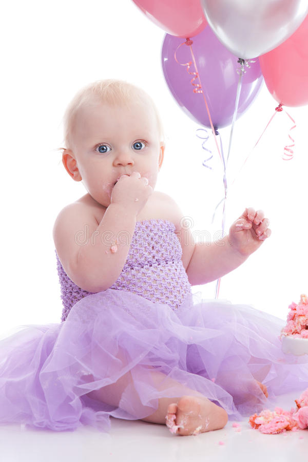 Birthday Girl. Adorable baby girl wearing a purple tutu dress and eating a pink birthday cake. Helium balloons in the background. Isolated on white stock images