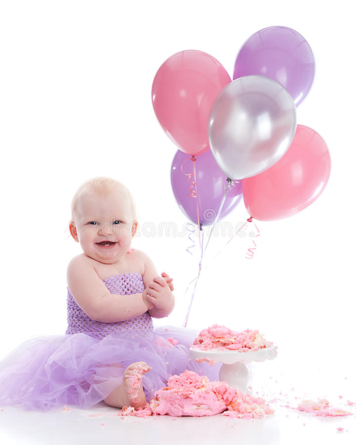 Birthday Girl. Adorable baby girl wearing a purple tutu dress and eating a pink birthday cake. Helium balloons in the background. Isolated on white stock image