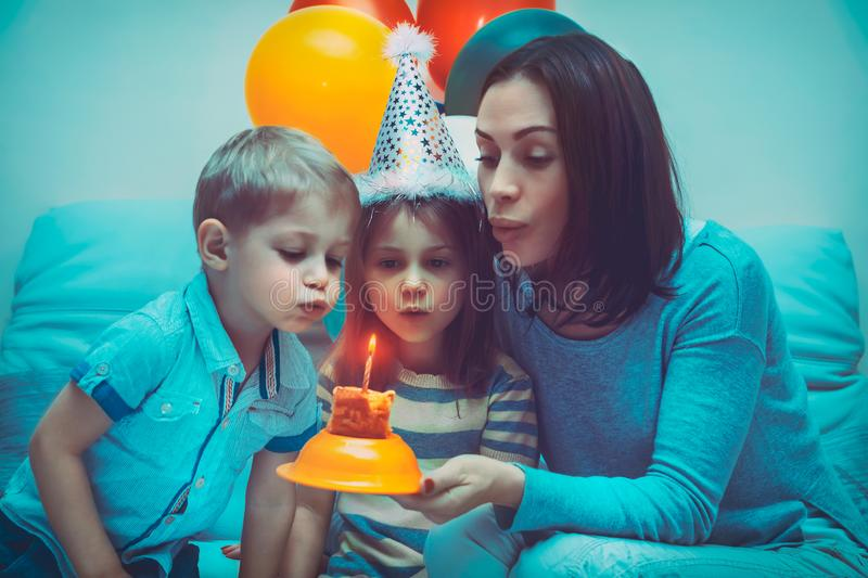 Happy birthday party. Birthday girl celebrating holiday with family, portrait of a beautiful young mother with two cute kids blow out candle on a festive cake royalty free stock image
